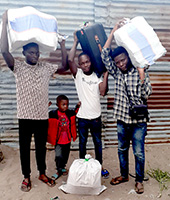 People helping at bus station with materials headed to Mukedi July 17